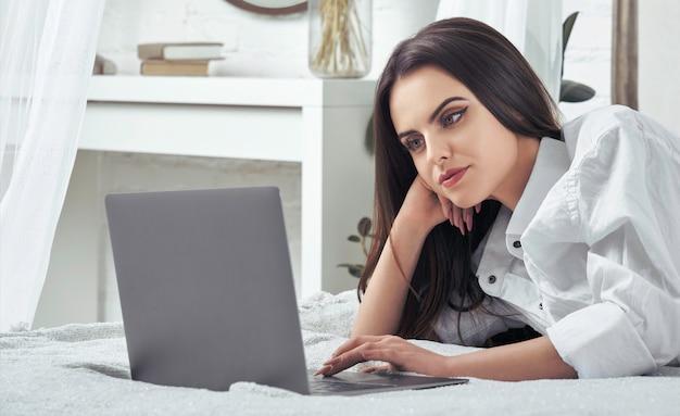 Dziewczyna używa laptop kłaść na łóżku. praca koncepcja domu dziewczyna pracuje w łóżku