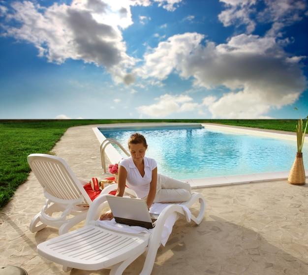 Dziewczyna używa laptop wzdłuż pływackiego basenu