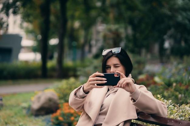 Dziewczyna używa mądrze telefon w miasto parka obsiadaniu na ławce