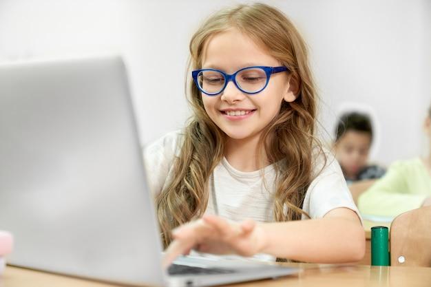 Dziewczyna używa nowożytnego komputer podczas lekci przy szkołą