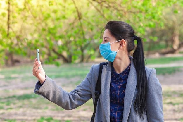 Dziewczyna używa smartfona i nosi ochronną maskę medyczną