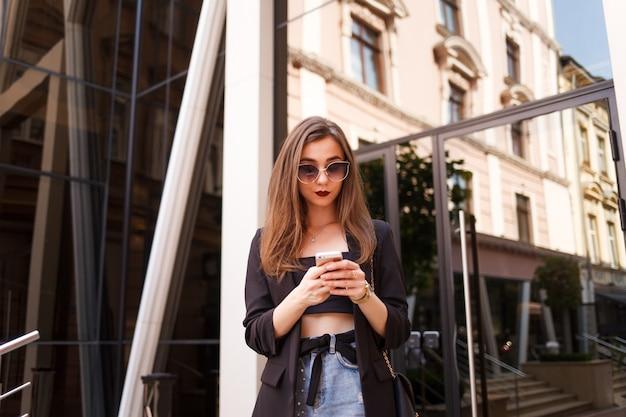 Dziewczyna używa smartfona na ulicy miasta