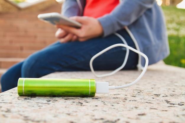 Dziewczyna używa smartfona na zewnątrz podczas ładowania z zewnętrznego banku energii