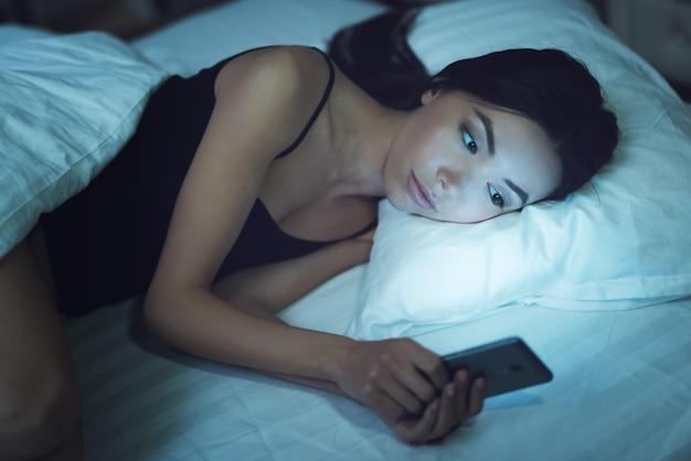 Dziewczyna używa smartphone na łóżku przed spać