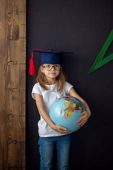 Dziewczyna w akademickim kapeluszu i okrągłych okularach stoi na czarnej ścianie