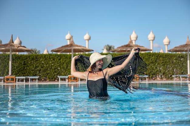 Dziewczyna w basenie w gorący słoneczny dzień