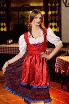 Dziewczyna w bawarskim odziewa w oktoberfest na karczemnym tle