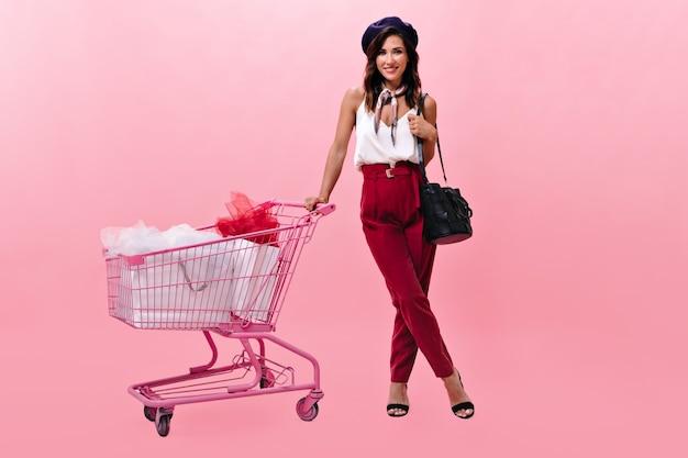 Dziewczyna w berecie uśmiecha się i pozuje z różowym wózkiem. piękna pani w bordowych klasycznych spodniach i śmiejącej się białej bluzce.