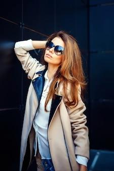 Dziewczyna w beżowy płaszcz i niebieskie dżinsy