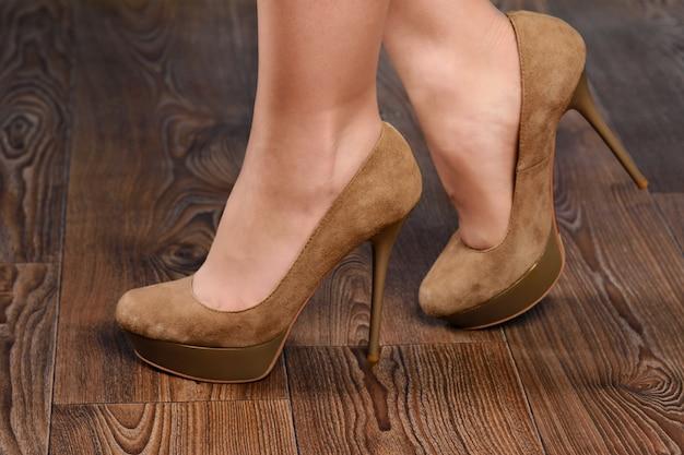 Dziewczyna w beżowych zamszowych butach na wysokim obcasie na drewnianej podłodze