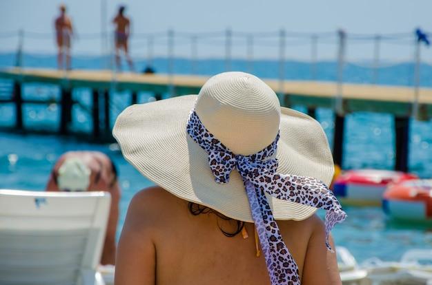 Dziewczyna w beżowym kapeluszu na plaży