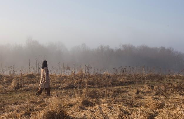 Dziewczyna w beżowym płaszczu chodzenie w słoneczny dzień