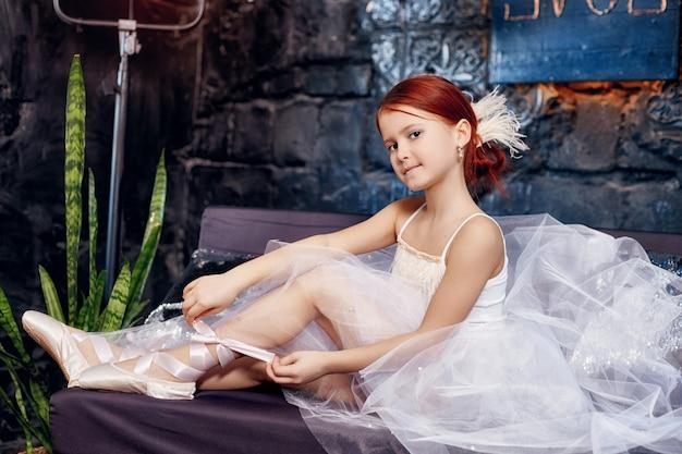 Dziewczyna w białej balowej sukni i butach, piękne rude włosy. młoda aktorka teatralna. mały balet prima