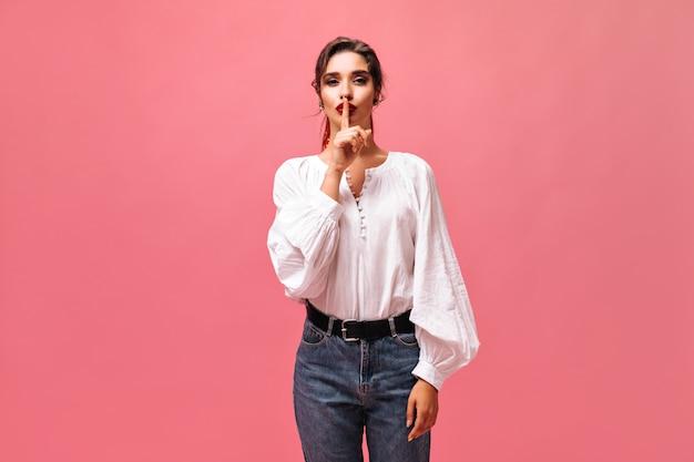 Dziewczyna w białej bluzce z prośbą o zachowanie tajemnicy. wspaniała dama z dużymi czerwonymi ustami w białej koszuli z długimi rękawami i dżinsach patrzy na aparat.