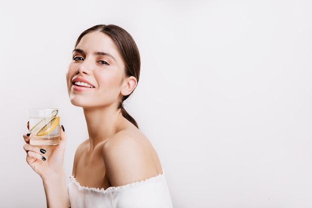 Dziewczyna w białej górze uśmiecha się i pozuje na odosobnionej ścianie. portret brunetka pije zdrową wodę z cytryną i ogórkiem.