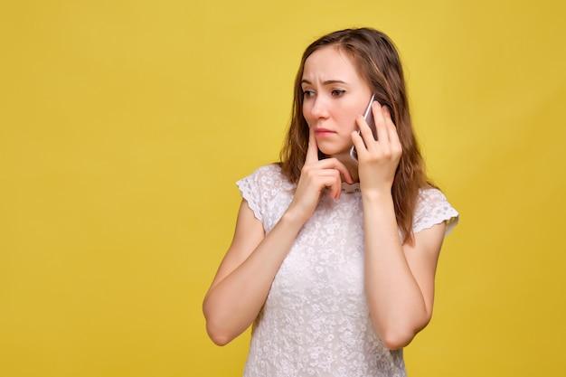Dziewczyna w białej koszulce i brązowych dżinsach na żółtym tle martwi się rozmową na smartfonie.
