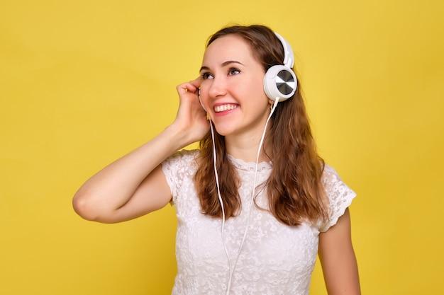 Dziewczyna w białej koszulce i brązowych dżinsach na żółtym tle relaksuje się i słucha muzyki za pomocą białych słuchawek.