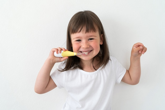 Dziewczyna w białej koszulce myje zęby elektryczną szczotką