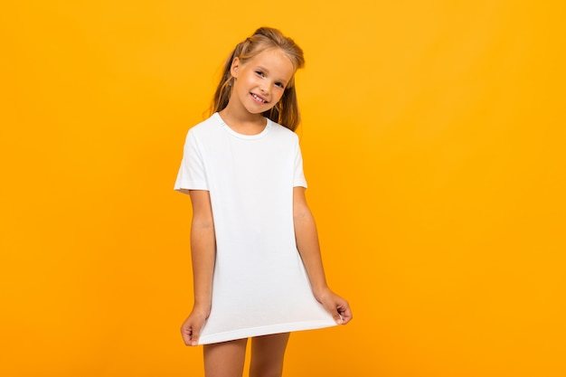 Dziewczyna w białej koszulce na żółtej ścianie