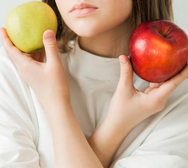 Dziewczyna w białej koszulce trzyma w rękach czerwone i zielone jabłka. kosmetyki naturalne i koncepcja zdrowej żywności. zdjęcie pionowe