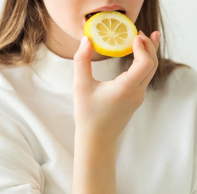 Dziewczyna w białej koszulce trzyma w rękach plasterek cytryny i gryzie go. zdjęcie pionowe