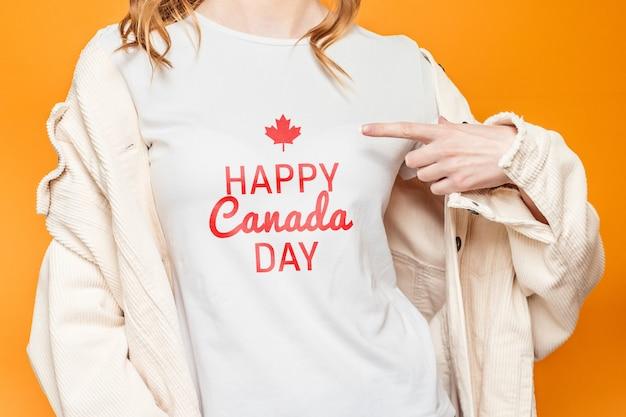 Dziewczyna w białej koszulce wskazuje palcem na słowa happy canada day na białym tle na pomarańczowym tle