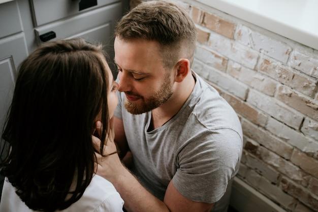 Dziewczyna w białej koszuli i facet w szarej koszulce w kuchni. pocałunek i przytulenie.