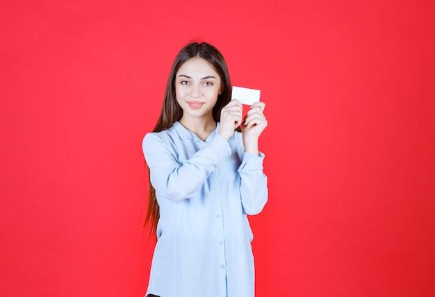 Dziewczyna w białej koszuli przedstawiając jej wizytówkę.