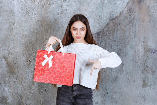 Dziewczyna w białej koszuli trzyma czerwoną torbę na zakupy i zaprasza osobę obok do zaprezentowania prezentu.