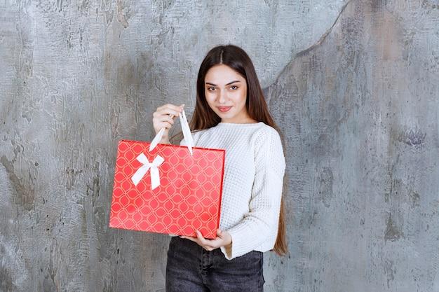 Dziewczyna w białej koszuli trzyma czerwoną torbę na zakupy.