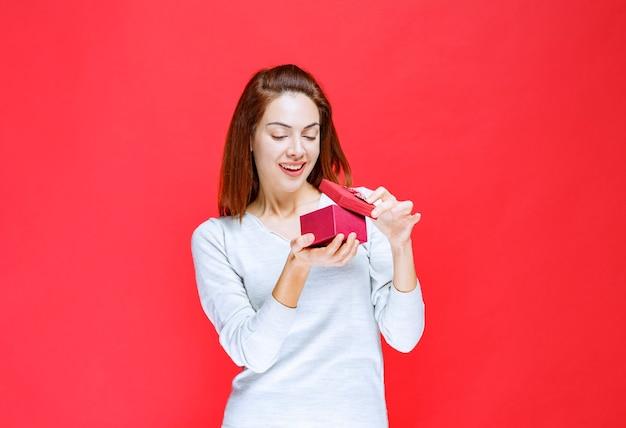 Dziewczyna w białej koszuli trzyma małe czerwone pudełko, otwierając je i dziwiąc się.
