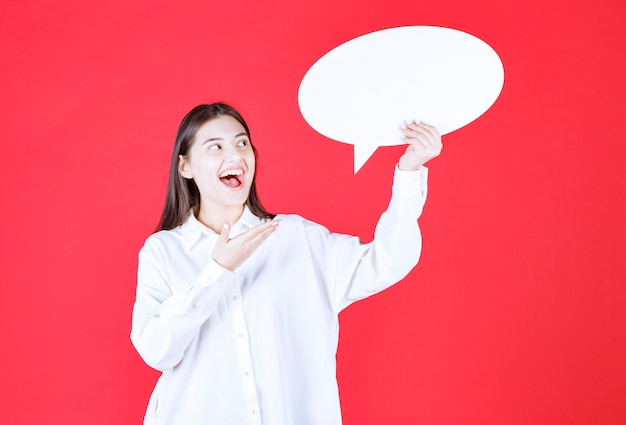Dziewczyna w białej koszuli trzyma owalną tablicę informacyjną i czuje się pozytywnie