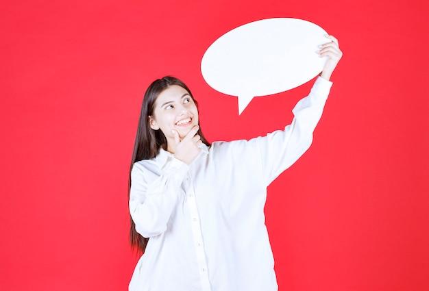 Dziewczyna w białej koszuli trzyma owalną tablicę informacyjną i wygląda na zdezorientowaną i zamyśloną