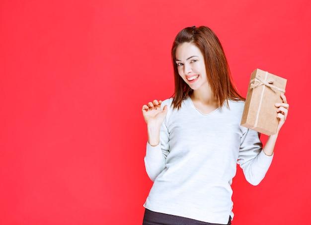 Dziewczyna w białej koszuli trzyma pudełko i wygląda na zdziwioną.