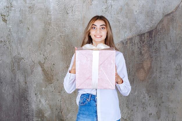 Dziewczyna w białej koszuli trzyma różowe pudełko owinięte białą wstążką.