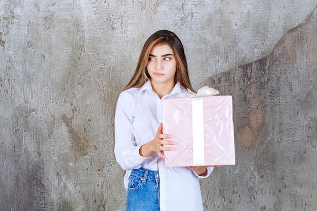 Dziewczyna w białej koszuli trzyma różowe pudełko upominkowe owinięte białą wstążką i wygląda na zdezorientowaną i niezdecydowaną