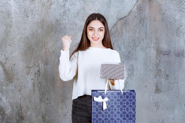 Dziewczyna w białej koszuli trzyma srebrne pudełko i niebieską torbę na zakupy i pokazuje pozytywny znak ręki.