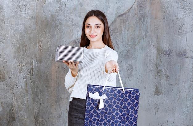Dziewczyna w białej koszuli trzyma srebrne pudełko i niebieską torbę na zakupy.
