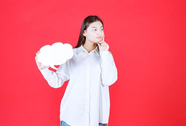 Dziewczyna w białej koszuli trzyma tablicę informacyjną w kształcie chmury i wygląda na zdezorientowaną i zamyśloną