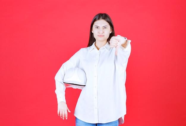 Dziewczyna w białej koszuli trzymająca biały hełm i pokazująca kciuk w dół