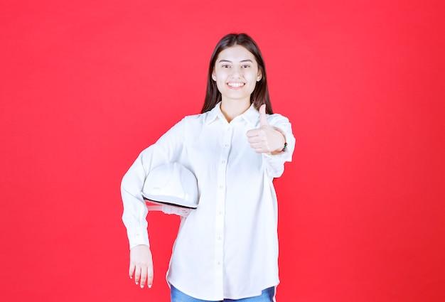Dziewczyna w białej koszuli trzymająca biały hełm i pokazująca pozytywny znak ręki