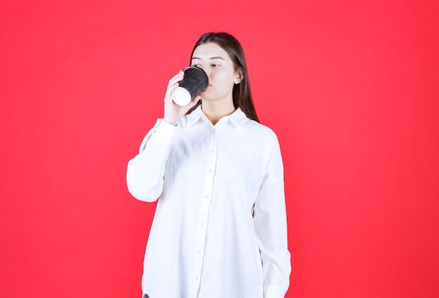 Dziewczyna w białej koszuli trzymająca czarną filiżankę kawy na wynos