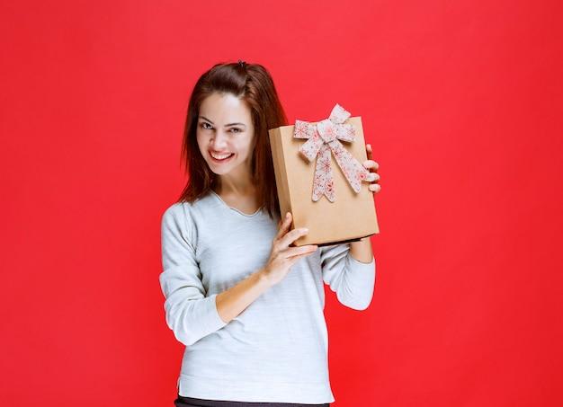 Dziewczyna w białej koszuli trzymająca kartonowe pudełko na prezent