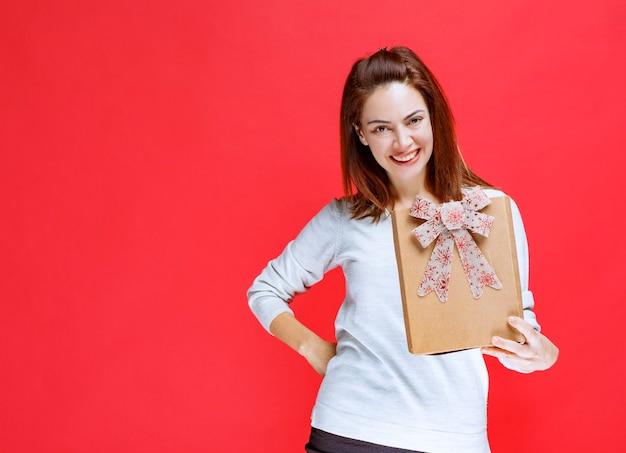Dziewczyna w białej koszuli trzymająca kartonowe pudełko prezentowe i prezentująca je komuś