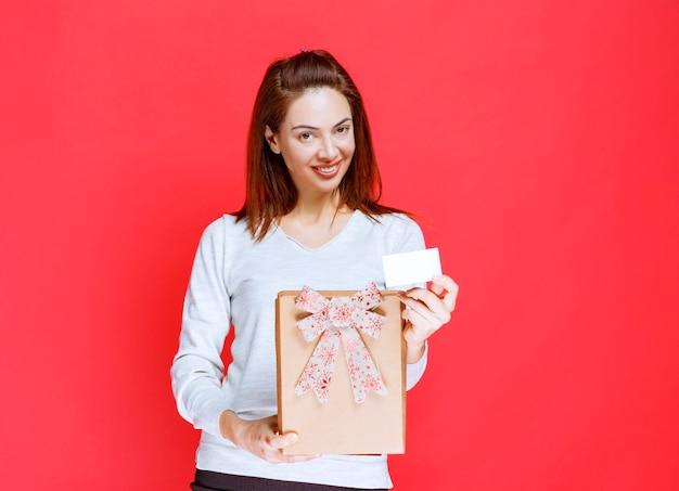 Dziewczyna w białej koszuli trzymająca kartonowe pudełko prezentowe i prezentująca swoją wizytówkę