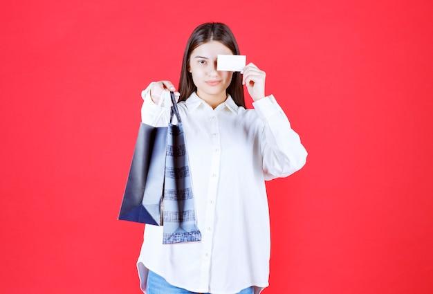 Dziewczyna w białej koszuli trzymająca kilka toreb na zakupy i prezentująca swoją wizytówkę