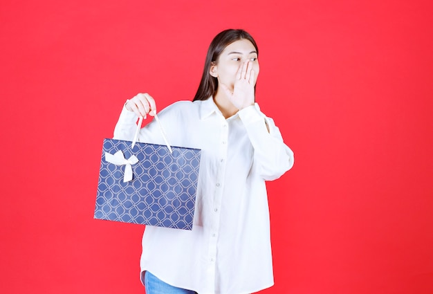 Dziewczyna w białej koszuli trzymająca niebieską torbę na zakupy i dzwoniąca do kogoś