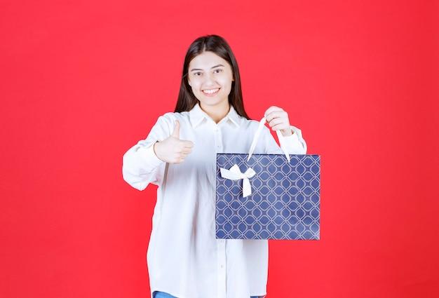 Dziewczyna w białej koszuli trzymająca niebieską torbę na zakupy i pokazująca pozytywny znak ręki