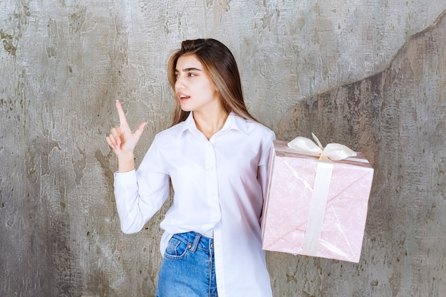 Dziewczyna w białej koszuli trzymająca różowe pudełko owinięte białą wstążką i mająca dobry pomysł.