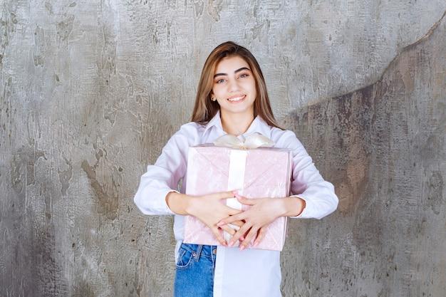 Dziewczyna w białej koszuli trzymająca różowe pudełko owinięte białą wstążką